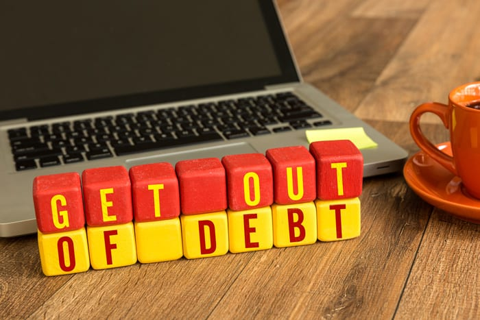 Get out of debt sign in front of computer