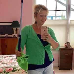 Michele Allen standing in client home working to pays off her debt