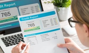 Woman reading credit report paper and online