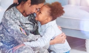 Happy military mother and daughter smiling and hugging