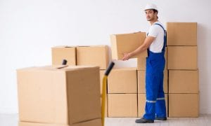 Young male professional mover doing home relocation with boxes in background